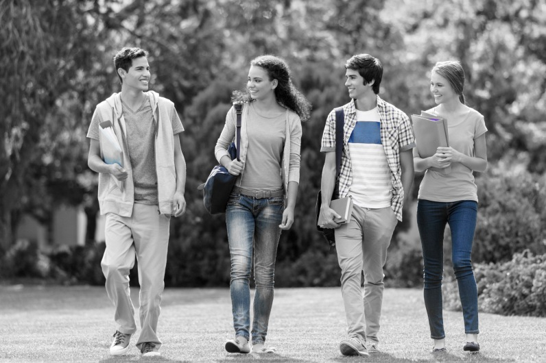 Teenage Students Looking At Friend While Walking On Campus
